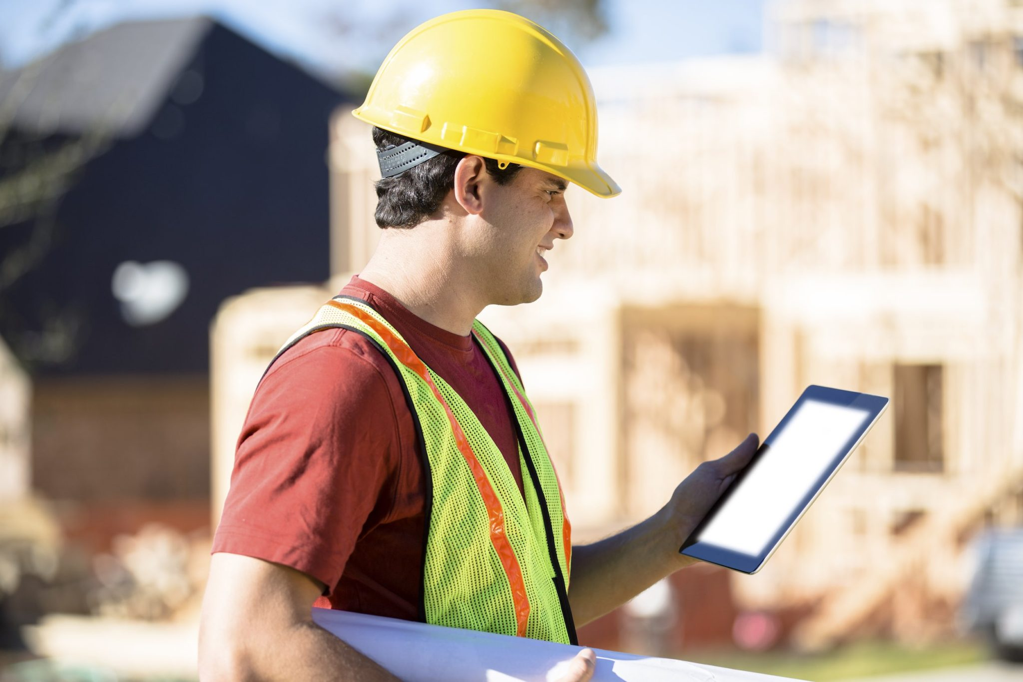 Supervisor on work site consulting project data using a handheld tablet